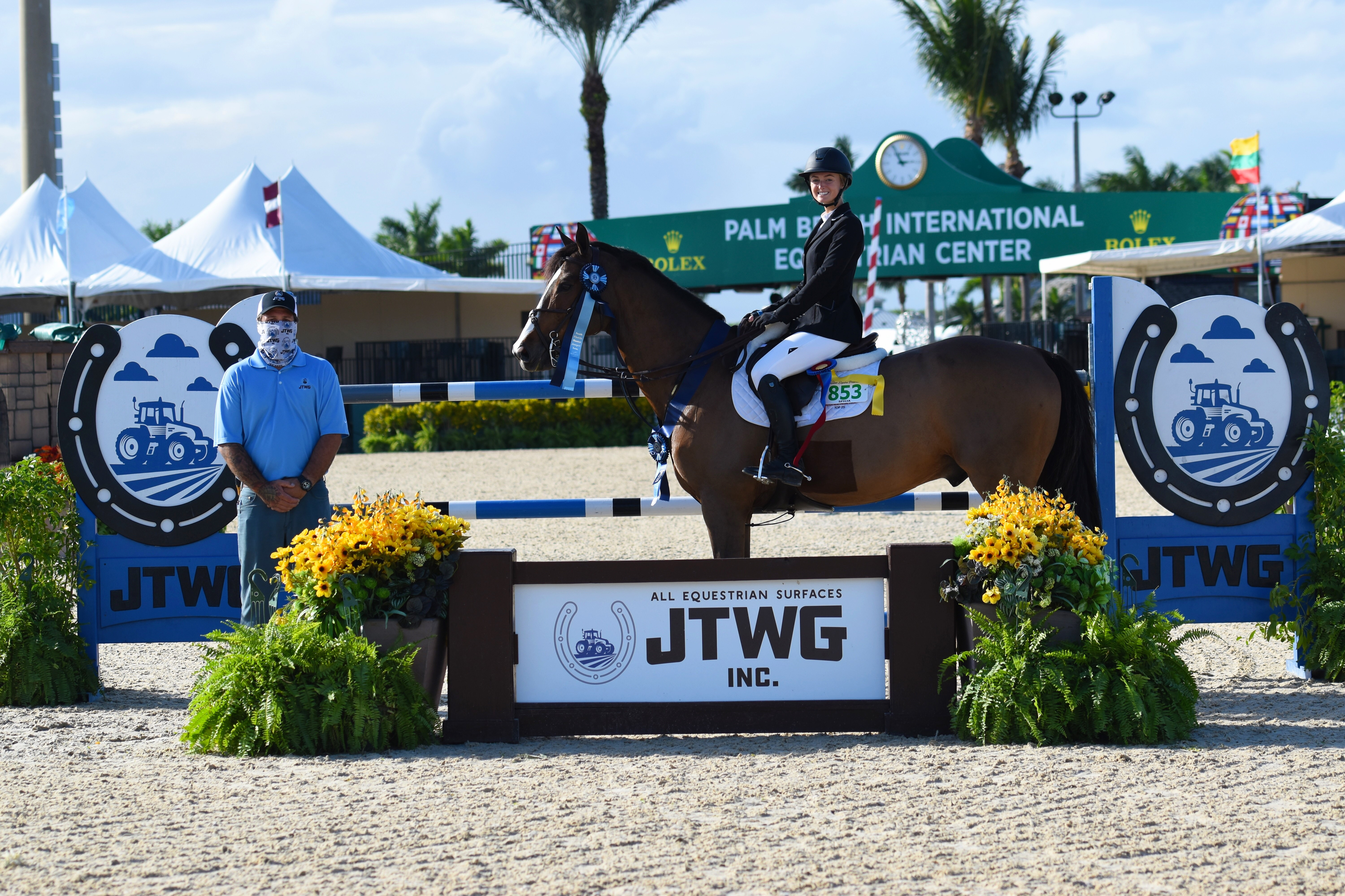 Catherine Wachtell, pictured on Coverboy with Travis Gould of JTWG, Inc., won the $10,000 High Junior/Amateur-Owner Jumper Classic, sponsored by JTWG, Inc, on Indy Van De Roten. ©PBIEC