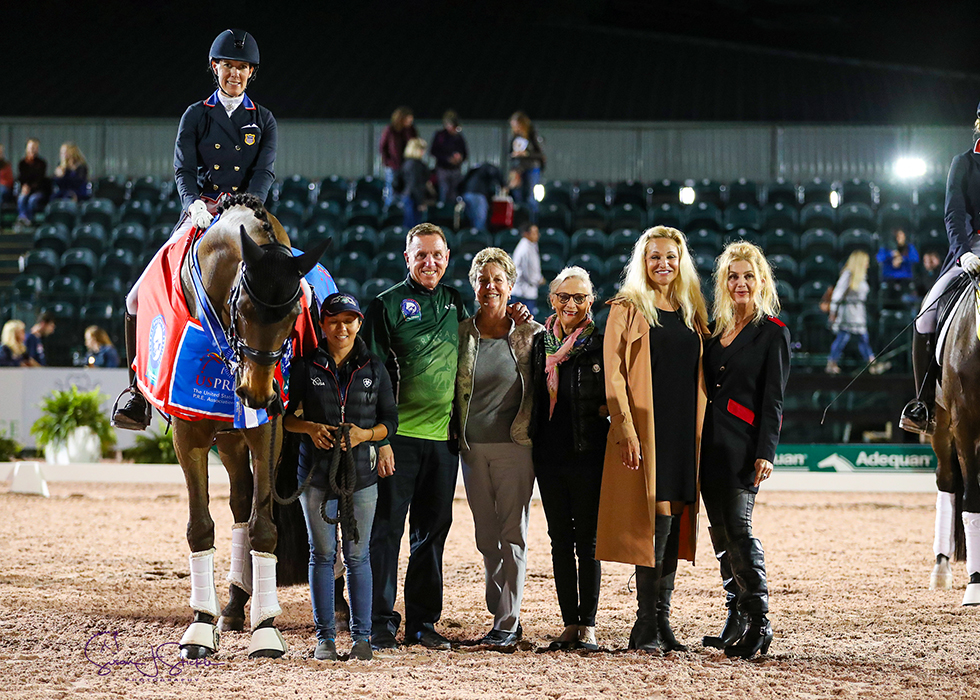 Olivia LaGoy-Weltz in the prize-giving with groom Nicole Ardito, Allyn Mann of Adequan®, judge Jane Weatherwax and Janne Rumbough, Kim Van Kampen and Jane Bistline of US P.R.E.. ©️Susan Stickle.